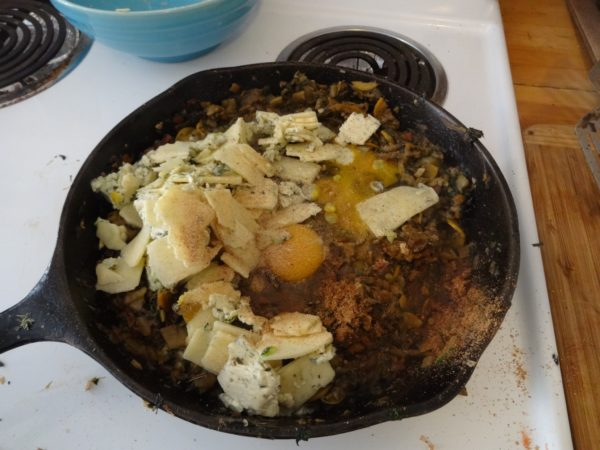 Add chopped parsley and/or other soft greens, salt, pepper, oregano, nutmeg, eggs, and cheese. Stir gently until mixed.