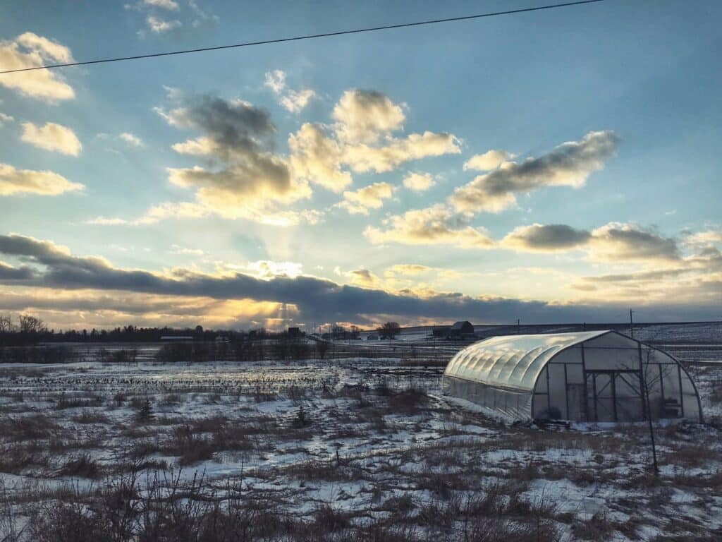 A Greenhouse Standing in an Icy Windswept Field, in front of a glorious sunset